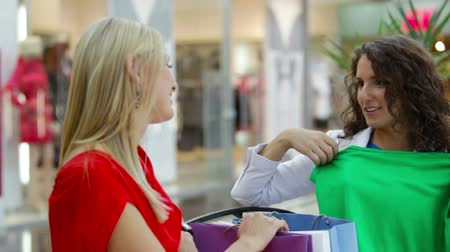наслаждаться : Shopping lady showing her purchases to her friends trying on a green garment Стоковые видеозаписи