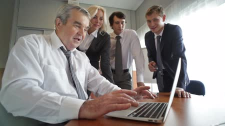 стремление : Senior businessman using laptop and sharing the results of the work with his younger associates