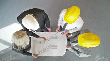architektonický : The above view of an engineering team discussing the blueprint
