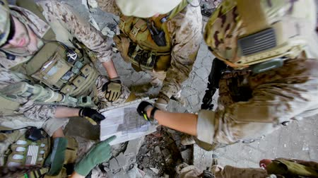 estratégico : The above view of a tactic military group discussing the map of the location Stock Footage
