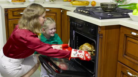 forno : Mom and daughter getting roasted turkey out of the oven