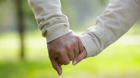 person's hand : Close-up of an elderly couple holding hands and walking together
