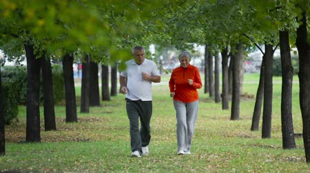 senior lifestyle : Retired couple keeping fit jogging in the park