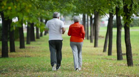 senior lifestyle : Couple of retirees running outdoors on a summer day Stock Footage