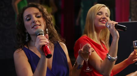 śpiew : Confident ladies singing karaoke in the club