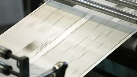 basın : Close-up of an uncut sheet of a black-and-white newspaper going through numerous rollers and cylinders