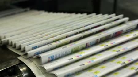 printings : Close-up of a conveyor carrying numerous freshly printed newspapers
