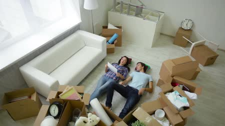 casal heterossexual : The above view of a peaceful young couple lying among unpacked boxes