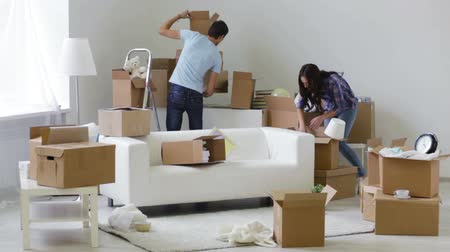 Домашняя жизнь : Caring young man helping his girlfriend with heavy unpacked boxes while moving home