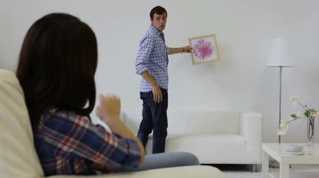 képek : Young man hanging the favorite picture of his girlfriend on the wall Stock mozgókép