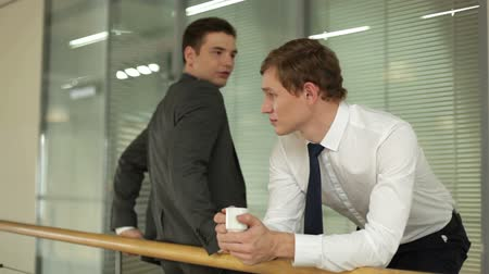 repousante : Two businessmen speaking during coffee break in the office building