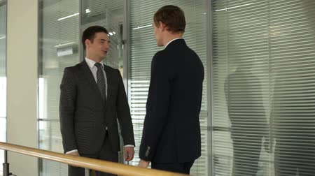 идущий : Two businessmen meeting and talking then going away in the office building