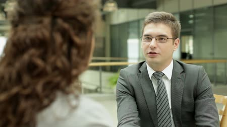 two people talking : Businessman interviewing young woman in the office Stock Footage