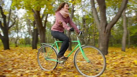 bisiklete binme : Cycling girl riding a bicycle ahead of the man walking through the autumn forest