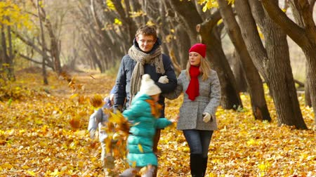 autumn : Married couple walking along the park lane, their children playing with golden leaves Stock Footage
