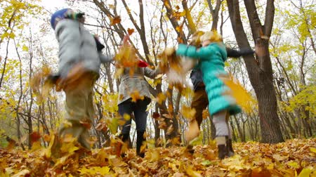 parenthood : Parents and kids having fun throwing about a big heap of autumn leaves