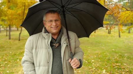 senior lifestyle : Senior man taking a walk on a rainy autumn day Stock Footage