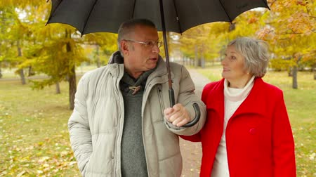 Elderly dates enjoying the walk in the park despite the rain 影像素材