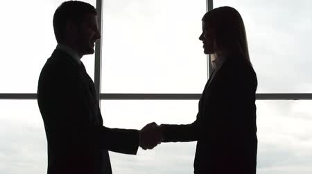 честолюбивый : Silhouettes of business partners greeting each other by a handshake and going off