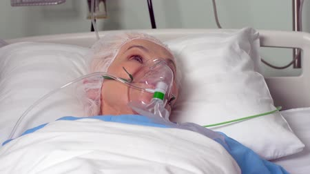 ér : Close-up of an elderly woman with an oxygen mask lying in bed before surgery