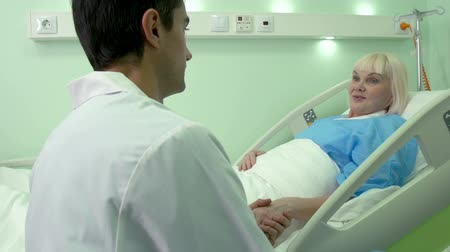 clínico : Compassionate young doctor holding hand of his patient with affection Stock Footage