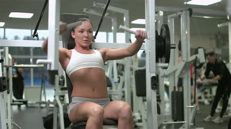 um : Muscular woman working out in the gym lifting weights