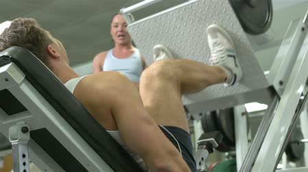 сильный : Female instructor watching sportsman training legs  Стоковые видеозаписи