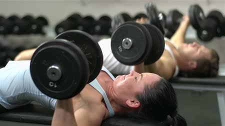 fisiculturismo : Male and female athletes lifting heavy dumbbells with effort