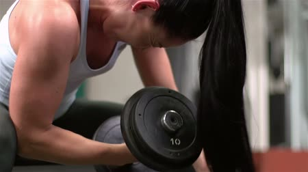 bicep : Close-up of a long-haired woman having intense bicep training