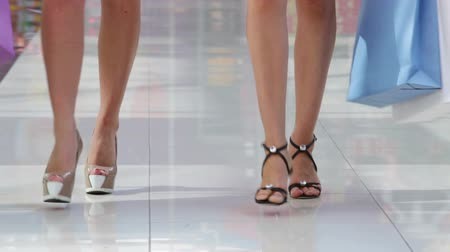 pięta : Shoppers walking like models across the mall floor towards the camera