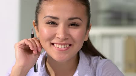 dişlek : Tilt up of a young office worker smiling cheerfully at the viewer Stok Video