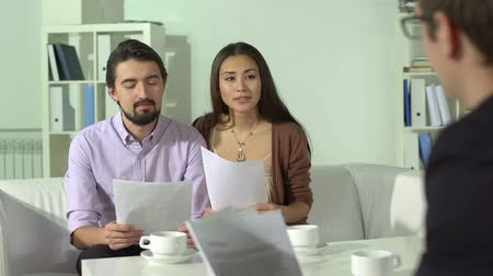 biztosítás : Married couple consulting with their personal financial advisor Stock mozgókép