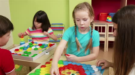 anaokulu : Cute preschoolers and their teacher making a puzzle picture with colorful pieces Stok Video