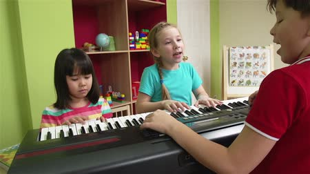 anaokulu : Little girl and her friends playing the piano and singing Stok Video