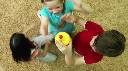przedszkole : The above view of cheerful kids playing with a colorful pyramid toy Wideo