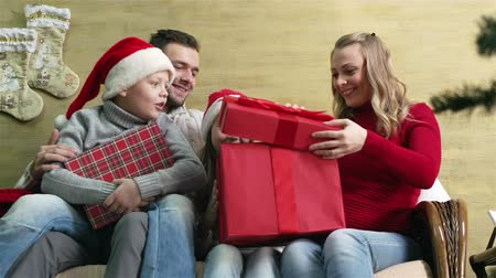 guy home : Happy family of four opening Christmas presents together