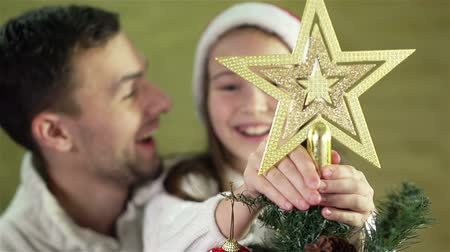 dad : Slow motion of an excited child and parent putting a golden star atop the fir-tree