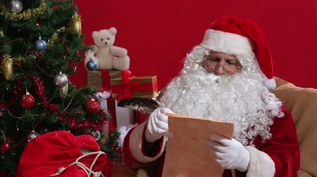 santa : Santa waking up from a short slumber and writing a letter Stock Footage