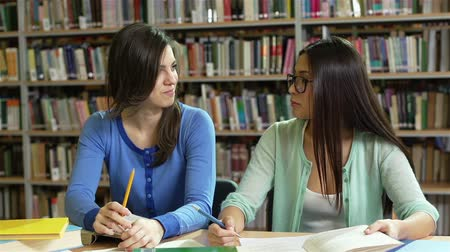 könyvtár : Students meeting at the library to do their homework and have a talk Stock mozgókép