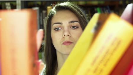 knihkupectví : Close-up of a student looking for a book in the library