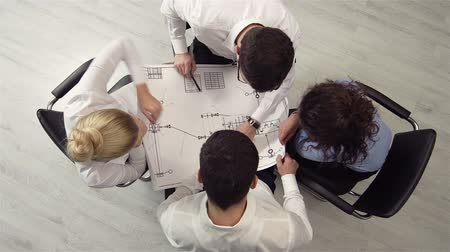 vállalkozó : The above view of an executive team reviewing a blueprint
