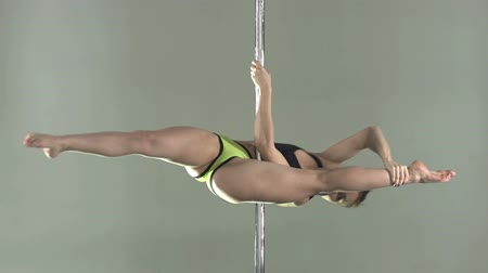 kutup : Fit young lady moving around the pole with energetic elegance   Stok Video