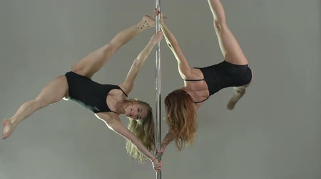 gymnasta : Cheerful friends dancing on the pole doing simultaneous exercises