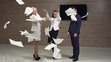 izgatott : Slow-motion of a cheerful business team standing among falling documents
