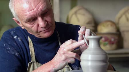 hrnčíř : Experienced potter creating a beautiful clay vase using professional tools