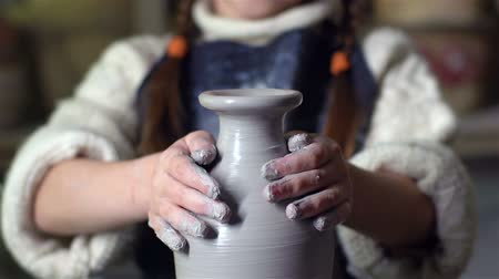 ceramika : Tilt up of a cute little girl making a clay jar on a pottery wheel