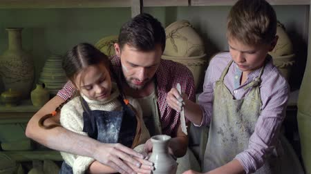 carinho : Dad and kids learning the basics of pottery in the workshop