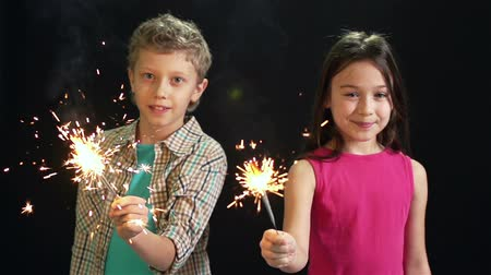 cintilante : Cheerful friends holding sparkling lights on a Christmas eve, isolated against black Stock Footage