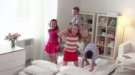 salto : Four energetic friends spending their weekend together jumping on the bed