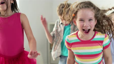 little : Close-up of children having pure fun jumping around, slow-motion Stock Footage